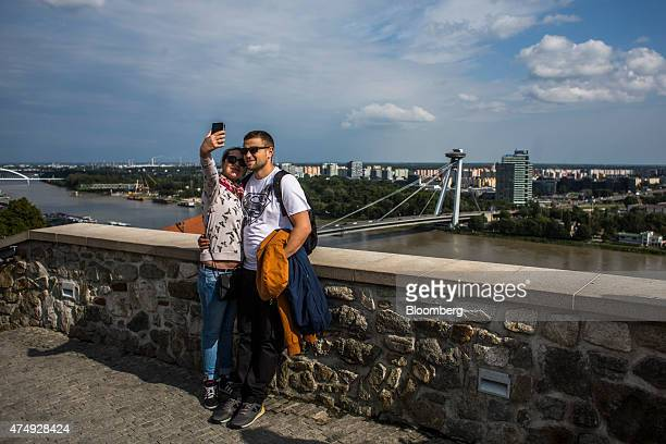 A couple takes a 'selfie' photograph as the Novy Most or New Bridge spans the Danube river with the city skyline beyond in Bratislava Slovakia on...