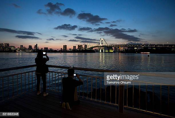 A couple takes photographs of the Rainbow Bridge using smartphones on a pier in the Odaiba area on May 12 2016 in Tokyo Japan