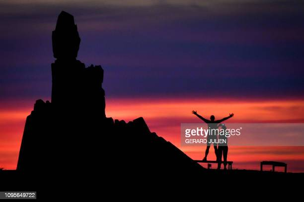 A couple takes pictures next to the Le Bateau Ivre monument honouring French poet Arthur Rimbaud by sculptor Jean Adamo as the sun sets over the...