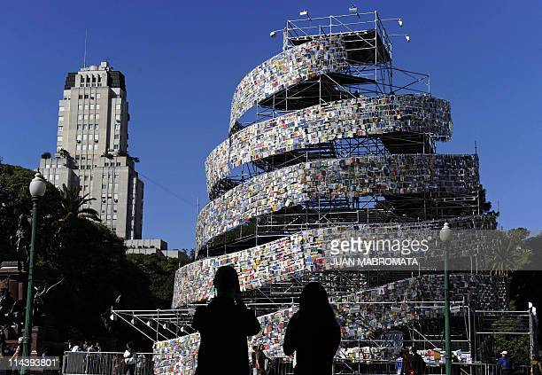 A couple takes pictures of the Tower of Babel a creation made by Argentine artist Marta Minujin with thousands of books in languages from all over...