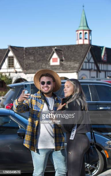 "Couple takes pictures with a mobile phone in Solvang, named ""the most Christmassy Town in America"" by Reader's Digest on December 20, 2020 in..."