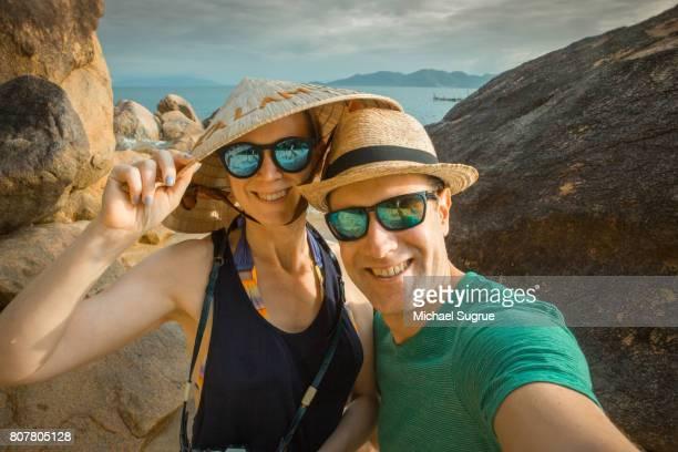 Couple takes selfie on the beach at sunset in Ninh Van Bay, Nha Trang, Vietnam.
