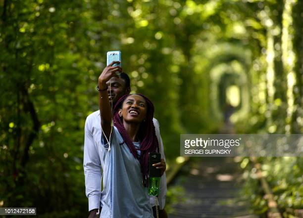 A couple takes selfies as they walk along former railway tracks surrounded by arches of intertwined trees in the socalled 'Tunnel of Love' near the...