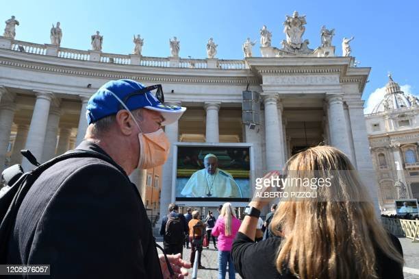 TOPSHOT A couple takes smartphone pictures of a screen livebroadcasting Pope Francis' Sunday Angelus prayer on St Peter's Square at the Vatican on...