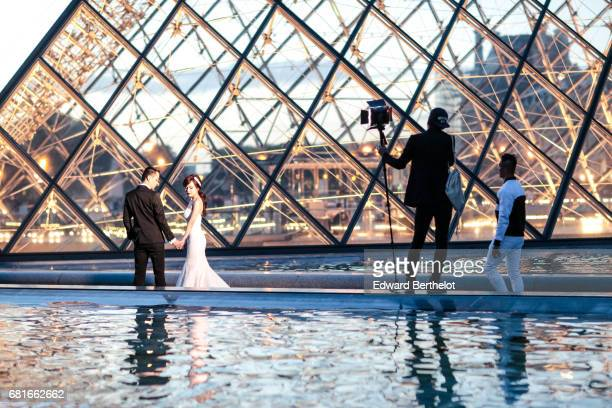 Couple takes wedding pictures at the Louvre in front of the Pyramid on September 25 2016 in Paris France All over the year couples come to take...