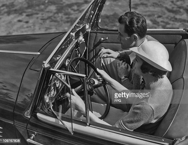 A couple taking a drive in a convertible car circa 1940's