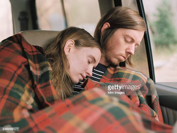 A couple taking a nap in their car, covered by a blanket.