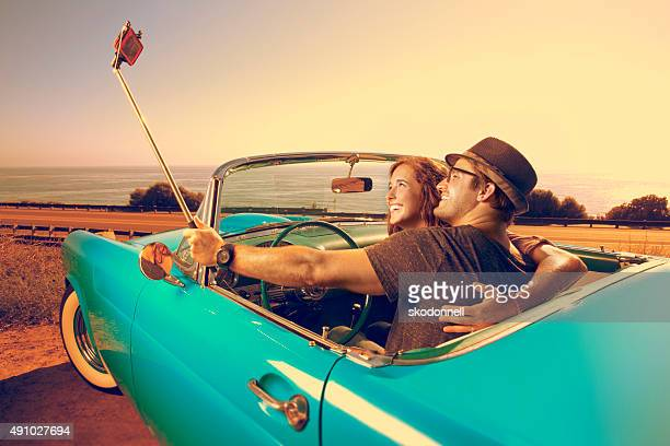Couple Taking a photo with  a selfie stick in a Convertible