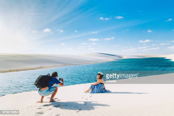 couple taking a photograph at lençois maranhenses - lencois maranhenses national park stock pictures, royalty-free photos & images