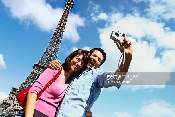 couple taking a photograph of themselves near the eiffel tower - travel14 stock pictures, royalty-free photos & images