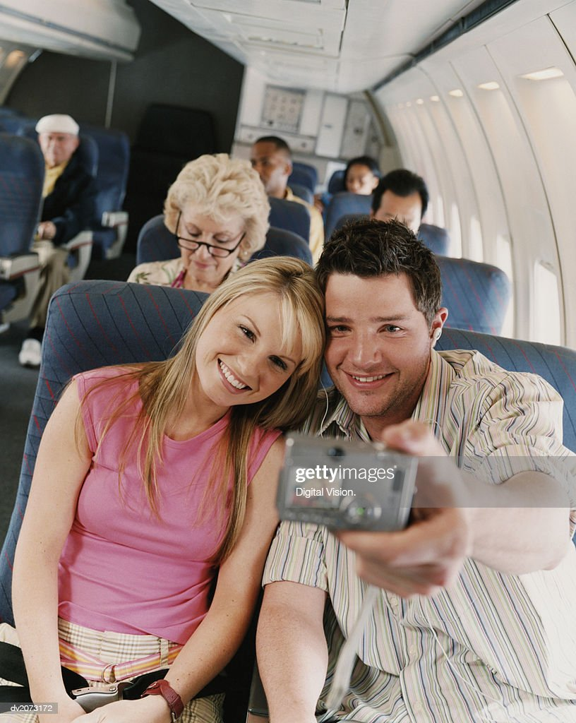 Couple Taking a Picture of Themselves in an Airplane : Stock Photo
