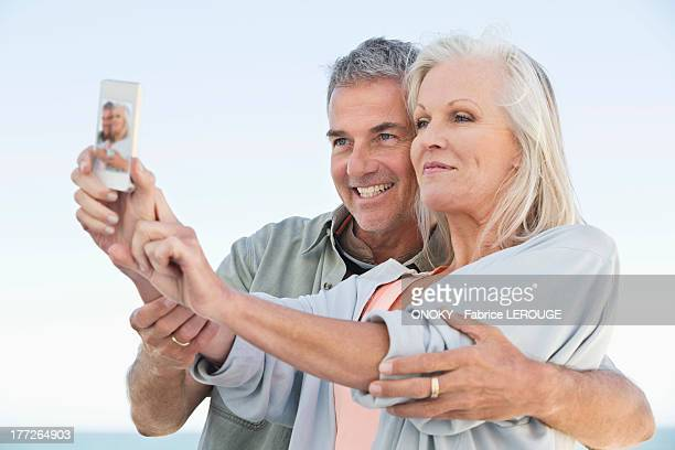Couple taking a picture of themselves with a cell phone on the beach