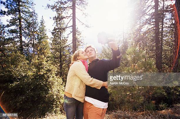 Couple taking a picture together in forest