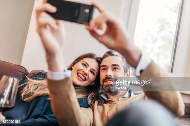 couple taking a selfie at home - mid adult couple stock pictures, royalty-free photos & images