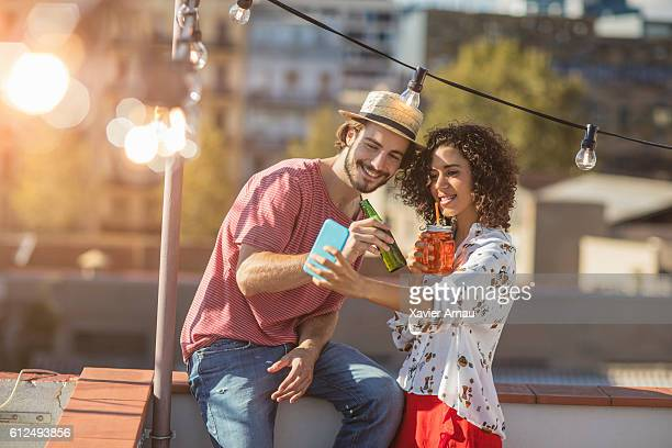 Couple taking a selfie at sunset on a rooftop party