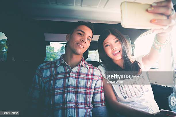 couple taking a selfie in the back of a car - self portrait photography stock pictures, royalty-free photos & images