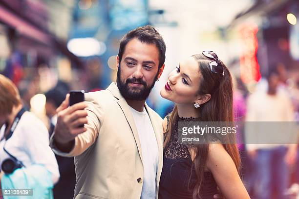 Couple taking a selfie on a busy city street