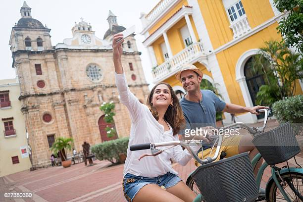 couple taking a selfie while sightseeing on bikes - cartagena colombia foto e immagini stock