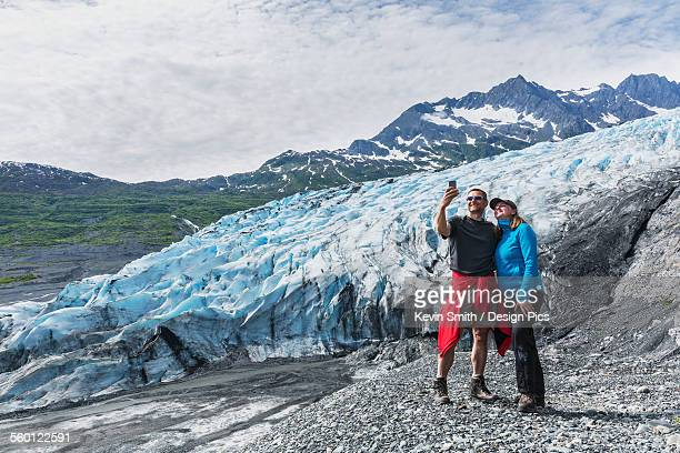 couple taking a self-portrait with a cell phone in front of shoup glacier, shoup bay state marine park, prince william sound - chugach mountains stock pictures, royalty-free photos & images
