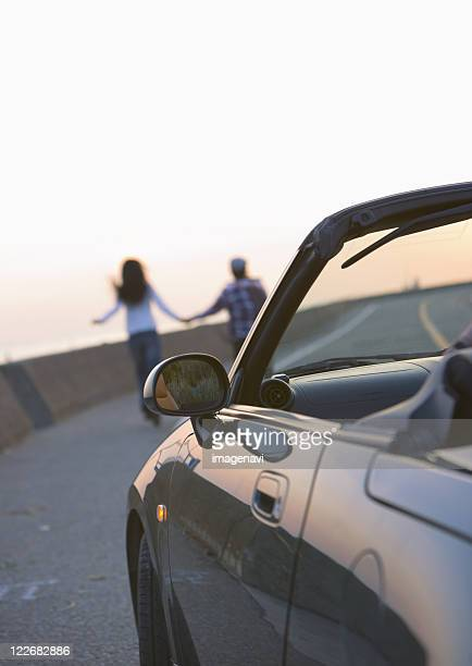 Couple taking a walk away from convertible