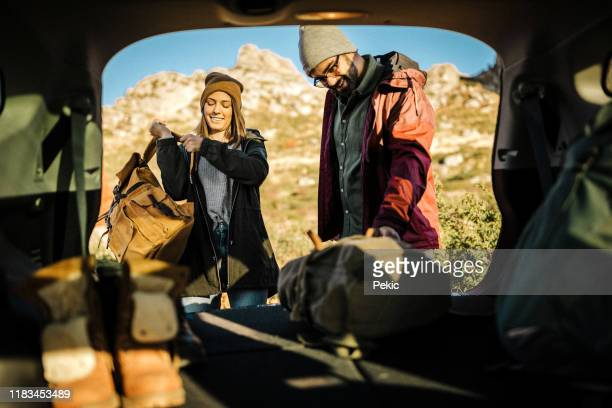 couple taking backpack out of car trunk in nature - packing stock pictures, royalty-free photos & images