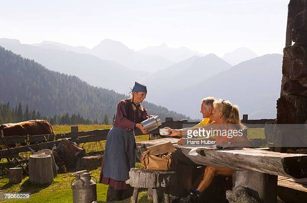 'Couple taking break at alpine hut, peasant woman serving them'