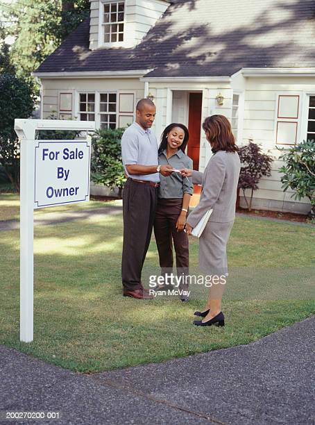 Couple taking business card from real estate agent on front lawn of house for sale