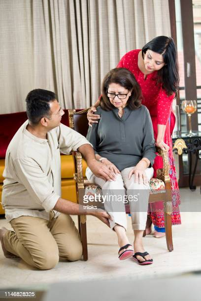 couple taking care of mother suffering with knee pain - mother in law stock pictures, royalty-free photos & images