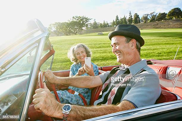 Couple taking cell phone photograph in classic convertible