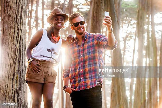 Couple taking cell phone picture in sunny forest