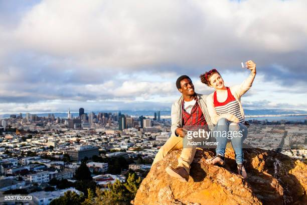 Couple taking cell phone selfie on rock overlooking cityscape