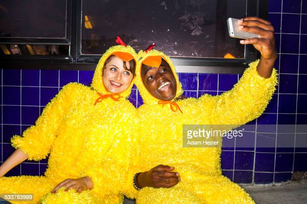 Couple taking cell phone selfies wearing chicken costumes