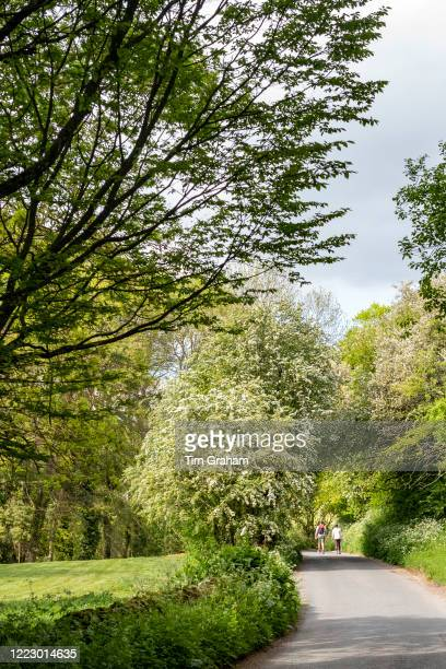 Couple taking daily exercise in Lockdown period walking in a country lane in The Cotswolds England during the Coronavirus COVID19 pandemic