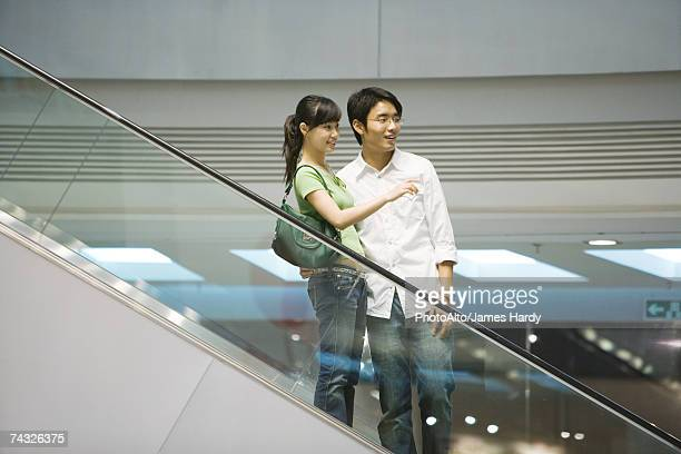 Couple taking escalator in shopping mall, woman pointing out of frame