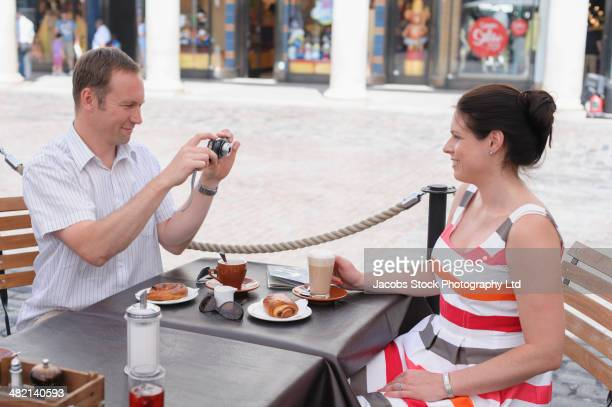 couple taking photograph at sidewalk cafe - travelstock44 stock pictures, royalty-free photos & images