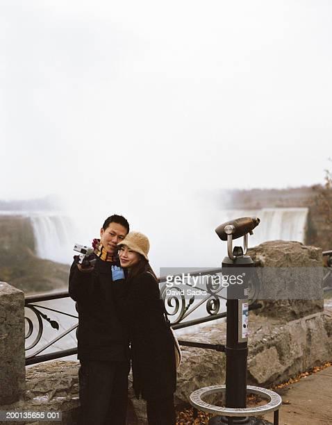 Couple taking photograph near waterfalls