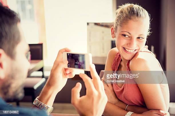 Couple taking photos each other at italian café