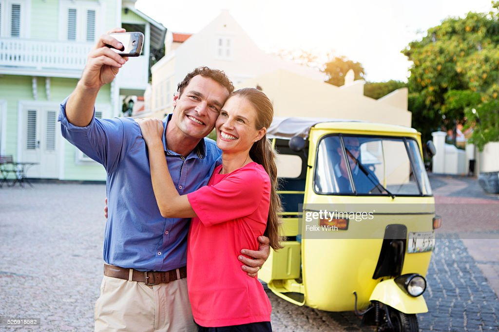 Couple taking picture in front of tuk tuk : Photo