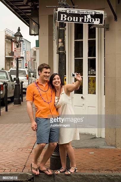 couple taking picture on bourbon street,  new orleans, louisiana, usa - ニューオリンズ バーボンストリート ストックフォトと画像
