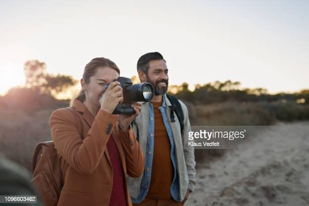 couple taking pictures on safari trip - photographe professionnel photos et images de collection