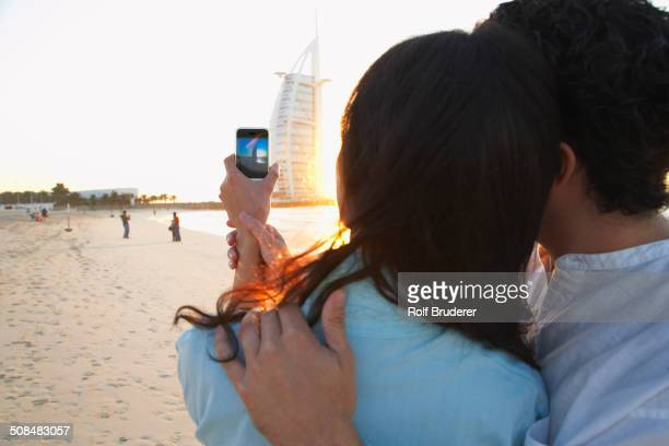 Couple taking pictures together on beach, Dubai, United Arab Emirates