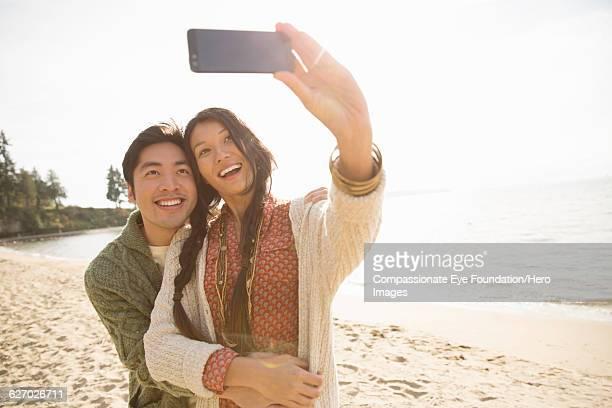 Couple taking self portrait on beach