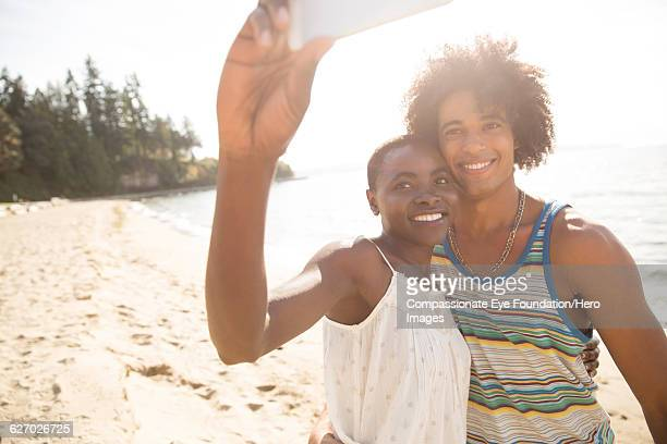 couple taking self portrait on beach - honeymoon stock pictures, royalty-free photos & images