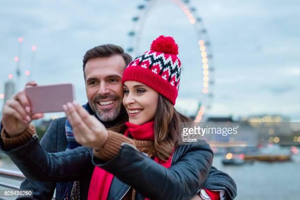Couple taking selfie against ferris wheel in london