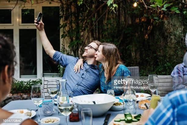 couple taking selfie at bbq with family - foco no segundo plano - fotografias e filmes do acervo