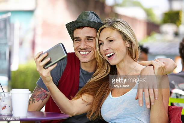 Couple taking selfie at cafe