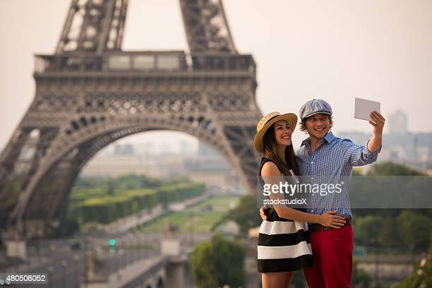 Couple taking selfie at the Eiffel Tower in Paris