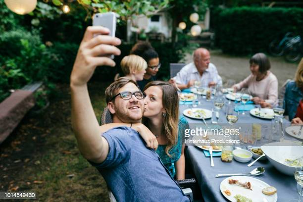 couple taking selfie during bbq with family - barbecue social gathering stock pictures, royalty-free photos & images
