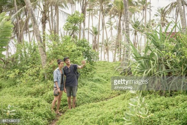 Couple taking selfie in lush forest, Sri Lanka