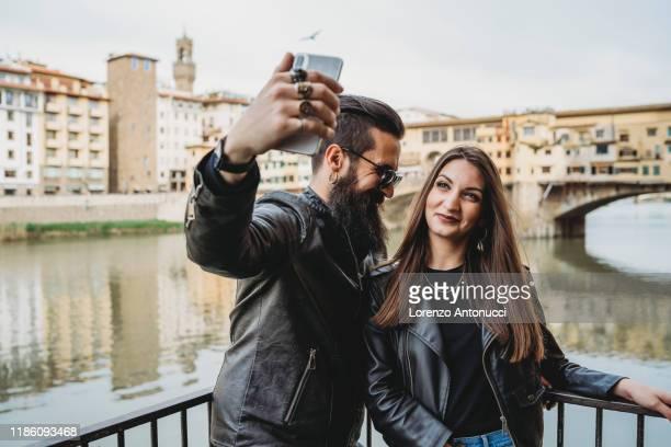 couple taking selfie on bridge, ponte vecchio, firenze, toscana, italy - レザージャケット ストックフォトと画像